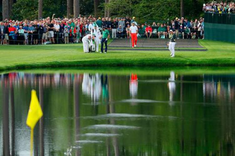 Rory McIlroy of Northern Ireland skips his ball across the pond on the 16th hole