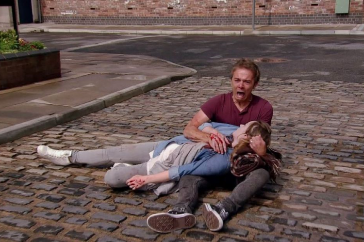 David cradles Kylie on the cobbles