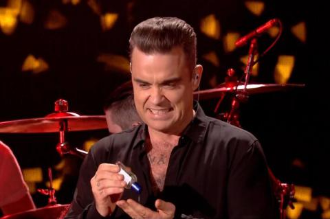 Robbie Williams grimaced and used hand gel after touching members of the crowd